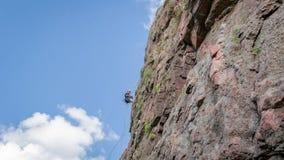 Yuzhnoukrainsk,乌克兰- 2018年6月19日:攀岩 一个年轻登山人攀登一个垂直的花岗岩岩石 极其体育运动 免版税库存图片