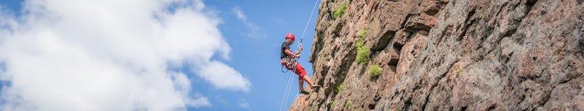 Yuzhnoukrainsk,乌克兰- 2018年6月19日:攀岩 一个年轻登山人攀登一个垂直的花岗岩岩石 极其体育运动 库存照片