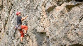 Yuzhnoukrainsk Ukraina - Juni 19, 2018: Vagga klättringen En ung klättrare klättrar en vertikal granit vaggar extrem sport Royaltyfria Bilder
