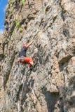 Yuzhnoukrainsk Ukraina - Juni 19, 2018: Vagga klättringen En ung klättrare klättrar en vertikal granit vaggar extrem sport Arkivfoto