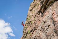 Yuzhnoukrainsk Ukraina - Juni 19, 2018: Vagga klättringen En ung klättrare klättrar en vertikal granit vaggar extrem sport Royaltyfri Bild