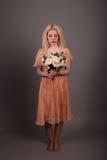 Żywa lali dziewczyna z kwiatami na szarym tle Fotografia Royalty Free