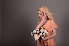 Żywa lali dziewczyna z kwiatami na szarym tle Fotografia Stock