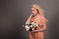 Żywa lali dziewczyna z kwiatami na szarym tle Zdjęcie Royalty Free