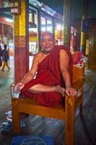 Smiling Buddhist Monk, Ywama, Inle Lake, Myanmar. YWAMA, MYANMAR - FEBRUARY 18, 2018: The portrait of smiling bhikkhu monk, sitting on chair with mug of lemonade Royalty Free Stock Photo