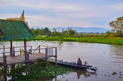 The view from porch of old monastery, Ywama, Inle Lake, Myanmar. YWAMA, MYANMAR - FEBRUARY 18, 2018: The view on waters of Inle Lake and floating farms from the Stock Images