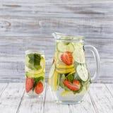 Żywienioniowy detox napój z cytryna sokiem, liśćmi w jasnej wodzie z lodem, czerwonymi truskawki, ogórkowych i nowych, fotografia stock