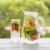 Żywienioniowy detox napój z cytryna sokiem, liśćmi w jasnej wodzie z lodem, czerwonymi truskawki, ogórkowych i nowych, obraz royalty free