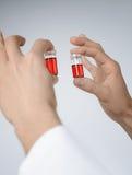 Ywo ciecza próbki w męskich rękach Zdjęcie Royalty Free