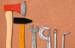 Yxa, hammare, skruvmejsel och skiftnycklar över kork Arkivbilder