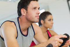 Yyoung man and woman working out at spinning class Stock Photography