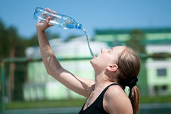 Yyoung woman drinking water after exercise Stock Photo