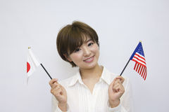 YYoung woman holding Japanese flag and American flag Stock Photography
