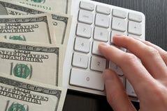 Zählung des Geldes auf Computerrechner lizenzfreie stockfotos