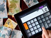 Zählung des Geldes auf einem Taschenrechner Stockbild