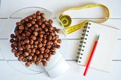 Zählung und die Fettmenge, das Protein, die Kalorien und die Kohlenhydrate in der Nahrung notierend Haselnuss auf Küchenskalen stockbilder