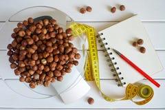 Zählung und die Menge des Proteins, der Kalorien, der Kohlenhydrate und der Fette in der Nahrung notierend Haselnuss auf Küchensk stockbilder