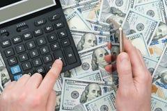 Zählung von Dollar auf Taschenrechner Lizenzfreie Stockfotos