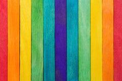 Zäunen Sie den hölzernen Regenbogen ein, der für hölzernen strukturierten Hintergrundgebrauch bunt ist Stockfotografie