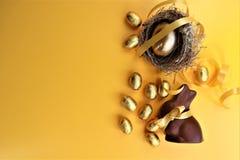 Złoci czekoladowi Wielkanocni jajka i czekoladowy królik na żółtym tle obrazy stock
