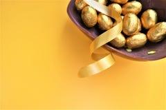 Złoci czekoladowi Wielkanocni jajka na żółtym tle zdjęcia royalty free