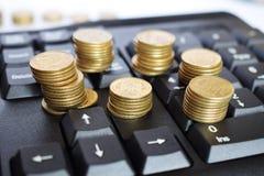 Złociste monety na klawiaturze, biznesowy pojęcie obraz royalty free