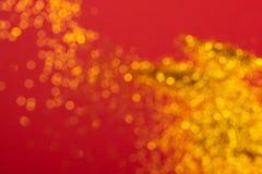 Złota blury błyskotliwość na czerwonym tle zdjęcia stock