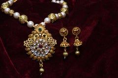 Złoto matrycująca biżuteria - Galanteryjny projektanta złoty długo ustawiający z kolczyka zbliżenia makro- wizerunkiem zdjęcie stock