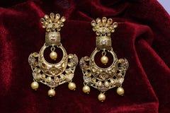 Złoto matrycująca biżuteria - Galanteryjnych projektantów złotych długich kolczyków makro- wizerunek zdjęcie royalty free
