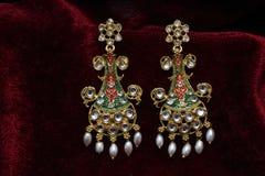 Złoto matrycująca biżuteria - Galanteryjnych projektantów złotych długich kolczyków makro- wizerunek zdjęcia royalty free