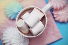 Zéphyr rose et blanc de guimauves avec la tasse de café ou de cacao sur une serviette rose Photos stock