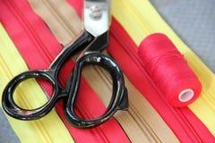 Zíperes, tesouras e um carretel da linha Fotos de Stock Royalty Free