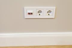 Zócalos eléctricos con un interruptor en la pared Foto de archivo