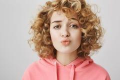 Zögernde attraktive junge Frau mit dem gelockten Haar, das Augenbrauen eine bei der Stellung mit den gefalteten Lippen, wünschend Lizenzfreies Stockfoto