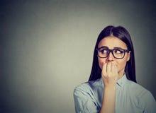 Zögernde Frau, die ihre Fingernägel sehnend für etwas oder besorgt beißt lizenzfreie stockfotografie