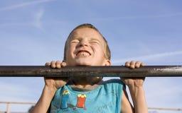 Züge des kleinen Jungen auf dem Stab. Lizenzfreies Stockfoto