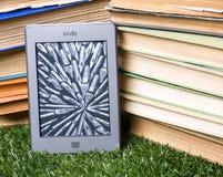 Zünden Sie Note E-Leser nahe bei Stapel Büchern an stockbilder