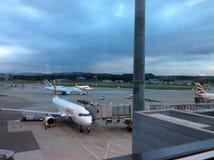 Zürich-luchthaven, Zwitserland, het Parkeren Vliegtuigen bij Schemering Stock Foto