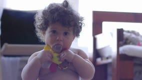 Ząbkować, kędzierzawy małej dziewczynki objadania brzęk i patrzeć w kamerę w pokoju na unfocused tle, zbiory wideo