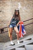 Zła dziewczyna trzyma kij bejsbolowego i Brytyjski zaznaczamy przy ulicą Obrazy Stock