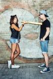 Zła seksowna młoda kobieta z rzemiennymi kotów ucho zagraża kija bejsbolowego faceta Zdjęcia Royalty Free