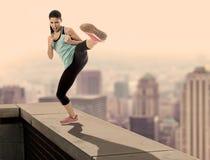 Złożony atrakcyjna wściekła sport kobieta w walce i sztuki samoobrony kopnięcia treningu na miastowej dach krawędzi z linii horyz Fotografia Royalty Free