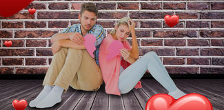 Złożony wizerunek atrakcyjnej potomstwo pary siedzący mienie dwa połówki złamane serce 3D Obrazy Stock