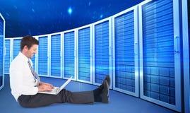 Złożony wizerunek biznesmen używa laptop i ono uśmiecha się Obrazy Royalty Free