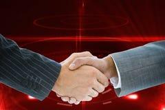 Złożony wizerunek biznesowy uścisk dłoni przeciw czerwonemu tłu zdjęcia stock