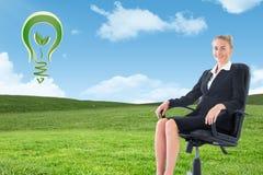 Złożony wizerunek bizneswomanu obsiadanie na swivel krześle w czarnym kostiumu Zdjęcia Stock