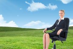 Złożony wizerunek bizneswomanu obsiadanie na swivel krześle w czarnym kostiumu Zdjęcie Royalty Free