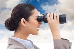 Złożony wizerunek boczny widok bizneswoman patrzeje przez lornetek Zdjęcie Stock
