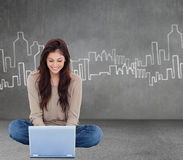 Złożony wizerunek brunetki obsiadanie na podłogowym używa laptopie Obrazy Royalty Free
