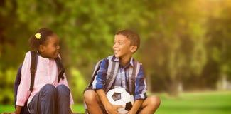 Złożony wizerunek chłopiec z przyjaciela mienia piłki nożnej piłką zdjęcie stock